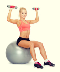woman with dumbbells sitting on fitness ball