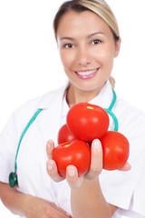 Junge Frau im Arztkittel mit Tomaten