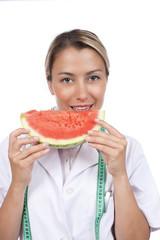 Junge Frau im Arztkittel mit Melone