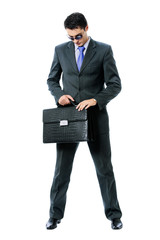 Businessman or hacker in sun glasses with briefcase, isolated