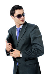 Businessman or hacker in sun glasses with laptop, isolated