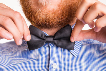 Bearded man ties a bow tie at the collar