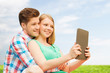 happy couple with tablet pc taking selfie outdoors
