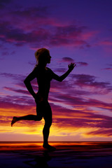 silhouette of a woman running in the sunset water