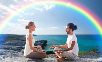happy couple meditating in lotus pose on beach