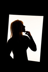 silhouette of woman in frame hand under chin