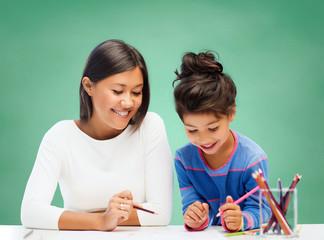 happy teacher and little school girl drawing
