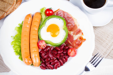 Egg fried in a green pepper, sausages, bacon and red beans