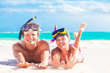 Cheerful happy couple having fun snorkeling, lying on summer