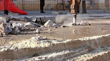 Hydraulic jack hammer is breaking concrete road