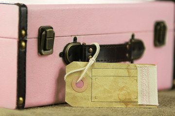 Pink retro vintage suitcase with blank paper tag