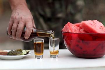 Person fills glasses of brandy