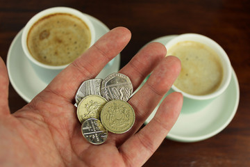 English Currency in hand with two coffee  in background.