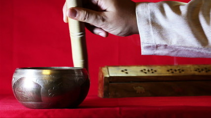 Tibetan singing bowl on the red background. With sound