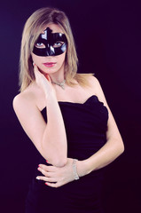 Beautiful girl in a black carnival mask
