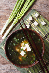 Japanese miso soup in a brown bowl vertical top view