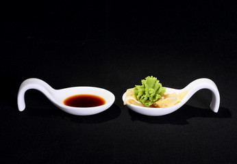 Wasabi and soy sauce on black background