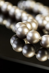 Close up Elegant Pearl Necklace on Glossy Table