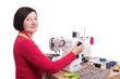 Woman seamstress at the sewing machine. Sews clothes.