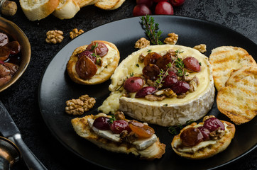 Brie cheese baked with nuts and grapes