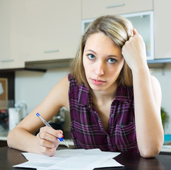 Serious woman with documents in kitchen