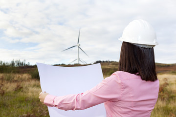 Back view of female engineer holding a blueprint at wind turbine