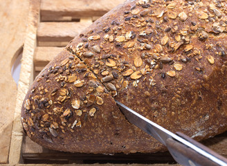 Knife Cutting Whole Grain Bread on cutting boar over white