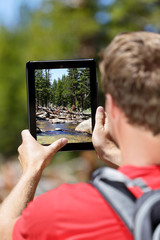 Hiking man taking nature pictures on tablet