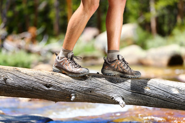 Hiking shoes - man hiker balancing crossing river