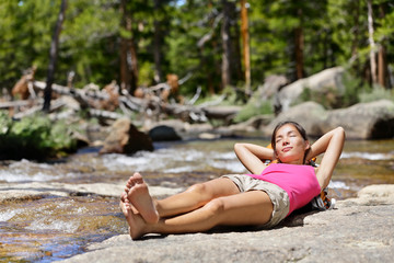 Relaxing woman hiker sleeping by river in nature