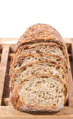 Sliced Whole Grain Bread on cutting board over white