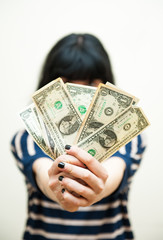 Brunette girl showing  money in hands selective focus