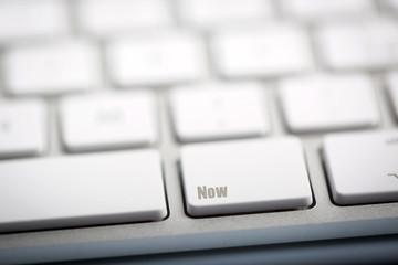 "The word ""Now"" written on keyboard"