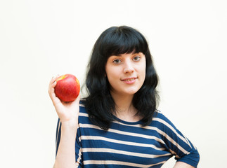 Smiling brunette girl shows red apple in her hands
