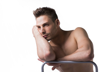 Naked young man sitting and resting on chair's back