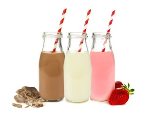 Various flavors of milk in bottles isolated on white