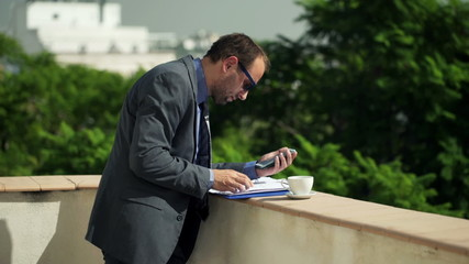 Businessman comparing data on smartphone and documents