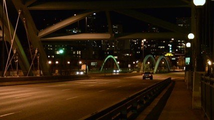 Cars traveling over a bridge into the city at night