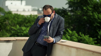 businessman using smartphone and drinking coffee on terrace