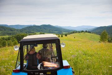 Man and woman farmers ride on the tractor in Russia