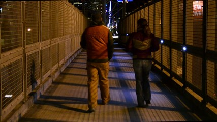 Pedestrians walking on a pedestrian bridge at night