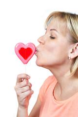 Happy girl kissing heart shaped lollipop