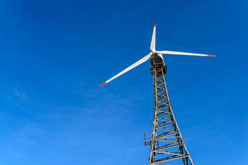 Wind turbine over blue sky background