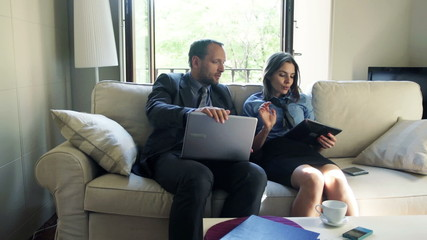 Business couple with tablet computer and laptop having break