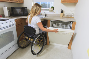 Woman with spinal cord injury opening dish washer