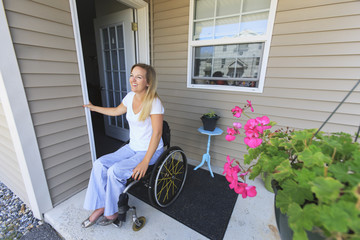Woman with spinal cord injury in wheelchair leaving her home