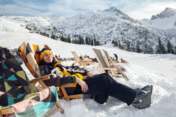 Man sits on sun-lounger in alpian ski resort