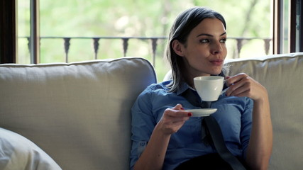 businesswoman drinking coffee sitting on sofa at home