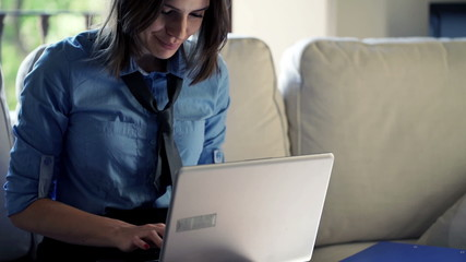 businesswoman working on laptop sitting on sofa at home