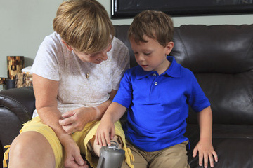 Grandson playing with grandmother's prosthetic limb